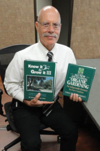 John Augelli in his office with two of his favorite books to read.